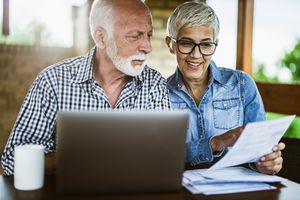 Mature couple reviewing investments on laptop at home.