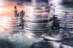 A double exposure image of the coin stack overlay with cityscape image.