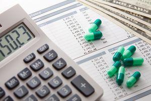 Image of a calculator, drug capsules, medical bills and dollar bills