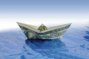 a paper boat made out of a $100 bill on paper water