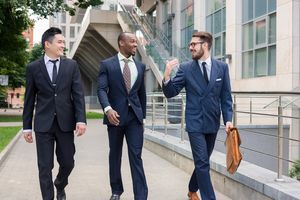 3 young men in suits, one with briefcase