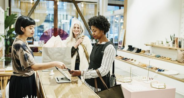 One Woman Paying Another Working as a Retail Salesperson as a Third Woman Looks on in a Retail Shoe Store.