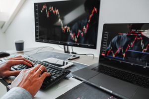Person trading stocks online using a laptop