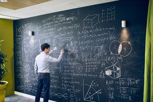 man doing math on a blackboard