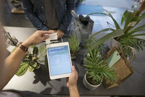 Cashier swiping digital tablet credit card payment in plant shop.