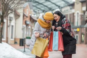 Two happy shoppers comparing purchases in shopping bags