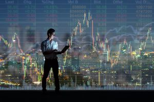 A businessman standing and using the smart mobile phone showing the stock market chart over the cityscape background at night time.