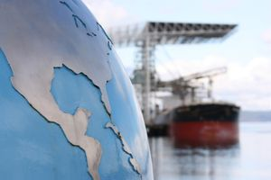 A globe with focus on the United States (USA) and Central America contrasted against a blurred background of a bulk cargo ship.