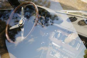 A Vintage Ferrari dashboard viewed through window.