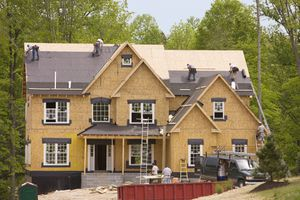 Builders Work on Large Home Being Built in Woodsy Area