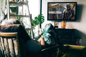 A person watches The Mandalorian on a wall mount TV.