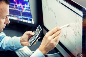 Stock market investor looking at chart on computer.