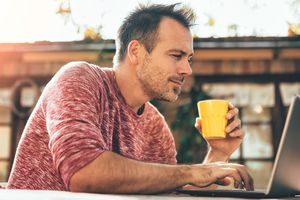 A man drinking coffee, looking at his laptop