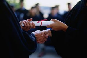 Person handing another a diploma and shaking hands.