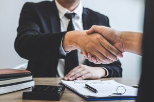 Cropped hands of real estate agent giving handshake to customer in office.