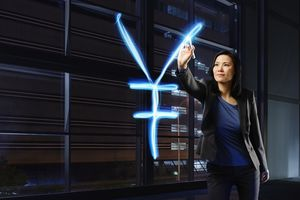 A businesswoman painting Yen sign with light.