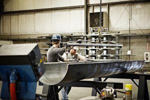 Steel workers adjusting position of formed steel