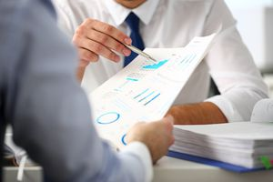 Group of businessmen with financial graph
