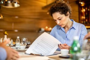 Young female entrepreneur writing on a paper document in a restaurant