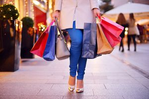 A young woman shopping in the city carrying paper bags.