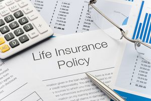 Close up of Life Insurance Policy with pen, calculator.
