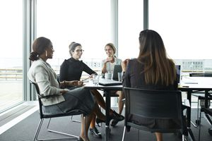 Four women sit around a conference table, holding a work meeting.