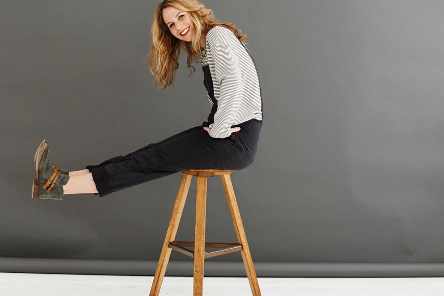 Woman sitting on a three-legged stool