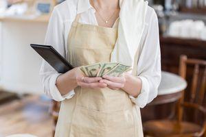 Unrecognizable Coffee Shop Waitress Counts Bill Payment