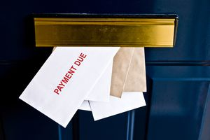 mailbox stuffed with letters with one saying payment due in red