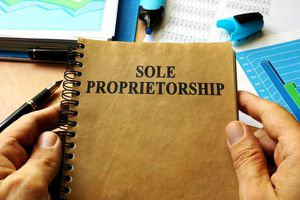 Hands holding book with title Sole proprietorship.
