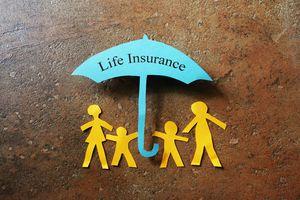 A paper life insurance umbrella over a paper family