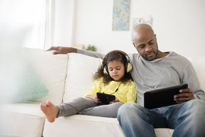 Parent and child, both using tablets while sitting on a white couch.