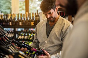Laughing Men Choosing Wine in Market