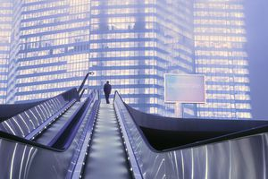 Businessman on Top of Moving Escalator at Illuminated Business District