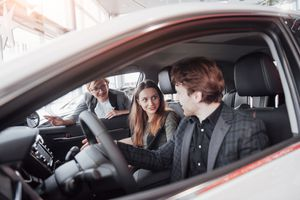 Happy beautiful couple is choosing a new car at dealership.