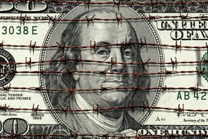 A hundred dollar bill with barbed wire around it