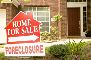 A foreclosure home for sale sign in front of a house