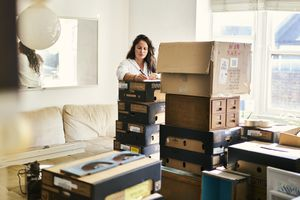 A woman labelling boxes in the process of packing to move house.