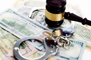 Judges gavel and handcuffs on american dollars