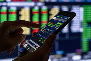 An investor makes a stock trade using a smart phone.