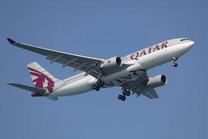 A Qatar Airways jet against a blue sky. The fuselage is grey and white with purple lettering.