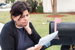 Woman by mailbox, reading letter with bad news