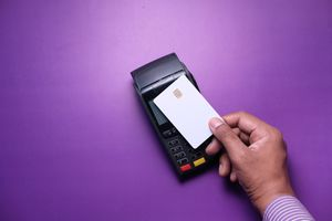Hand holding a credit card touching a card reader for payment