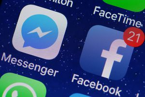 In this photo illustration, the logo of the Messenger and Facebook applications are displayed on the screen of an Apple iPhone on April 06, 2018 in Paris.