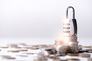 the abstract image of the coin stack which has the padlock on top and white copy space. the concept of saving, business, financial, cyber security and digital crime.