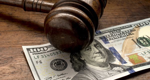 Wooden gavel on top of $100 bill