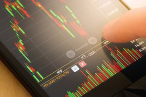 A person checking a stock chart on a smartphone.