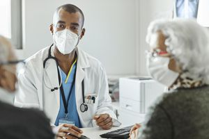 Doctor discussing with elderly couple during COVID-19 outbreak. Male healthcare worker is explaining senior man and woman while sitting at desk in clinic. They are in protective face masks.