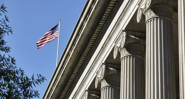 U.S. flag flying over the Treasury Department building, which is in a neoclassical design