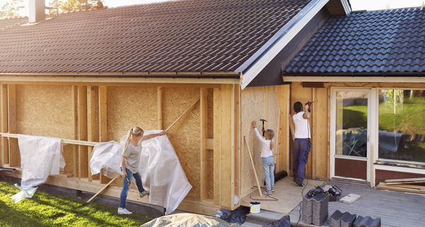 Family using hammer on walls of house being renovated